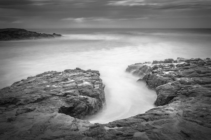 rock formation slow motion water beach black white