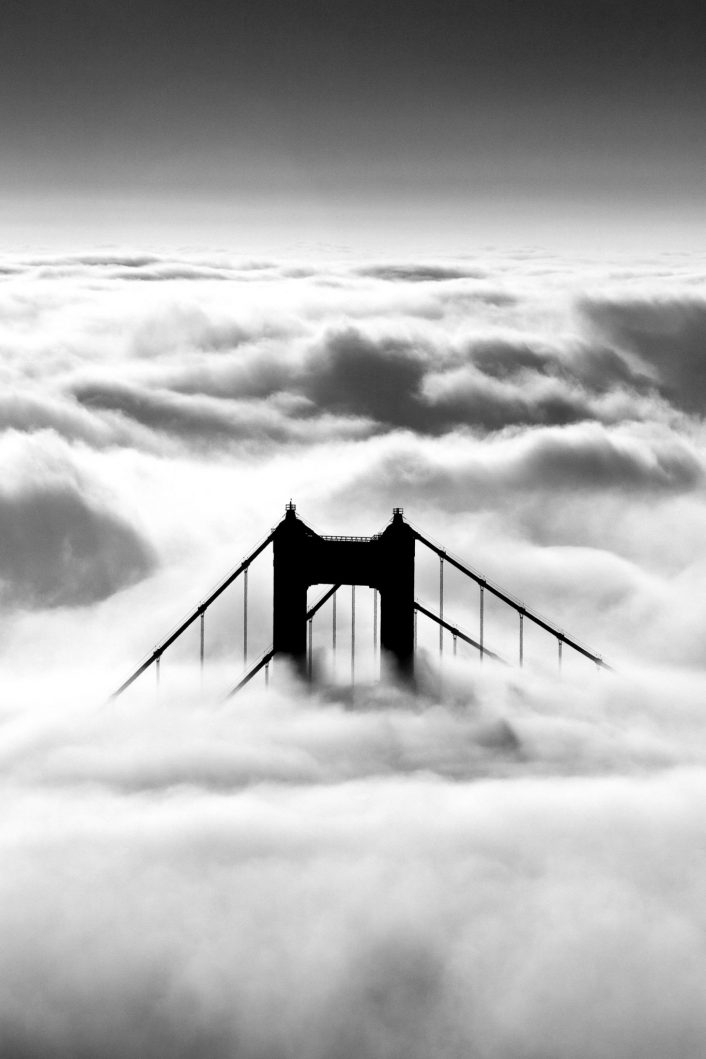 The Mighty Golden Gate Bridge stands tall above the fog at sunrise