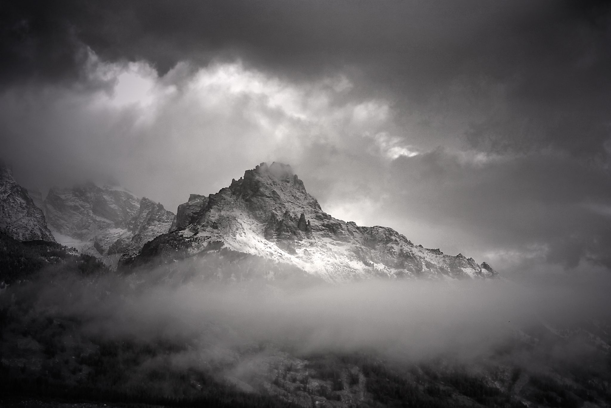 """The """"Sisters"""" (the little peaks in the middle of the mountain) endure a stormy morning in the Tetons"""